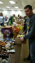 Dustin Leck helps Blue Star Mothers pack care packages for soldiers serving overseas. Leck received similar packages when he served in Afghanistan.