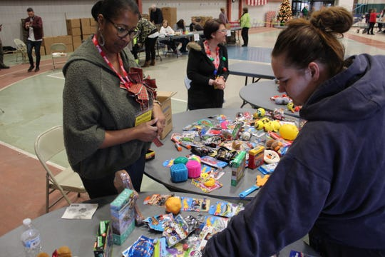Laura Wetzel of Clyde, right, picks out toys as Community Christmas board members Cassandrea Tucker, left, and Becky Holtgreven help at Wednesday's Community Christmas event at Terra State Community College.