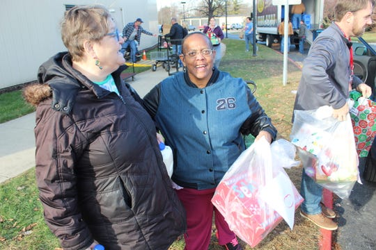 Ann Rusin, left, and Brenda Thompson of Fremont pick up food and gift donations at the annual Community Christmas held at Terra State Community College Wednesday.