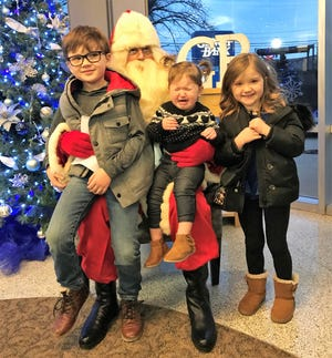 Henry, Amelia and Cora Swiech pose with Santa Claus at GenoaBank on Dec. 11.