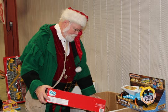Sandusky County Community Christmas Chairman John Havens, dressed as Santa Claus, sorts through toys Wednesday at Terra State Community College's Student Activities Center. Community Christmas celebrated its 25th year with toy, clothing and food donations to hundreds of community members.