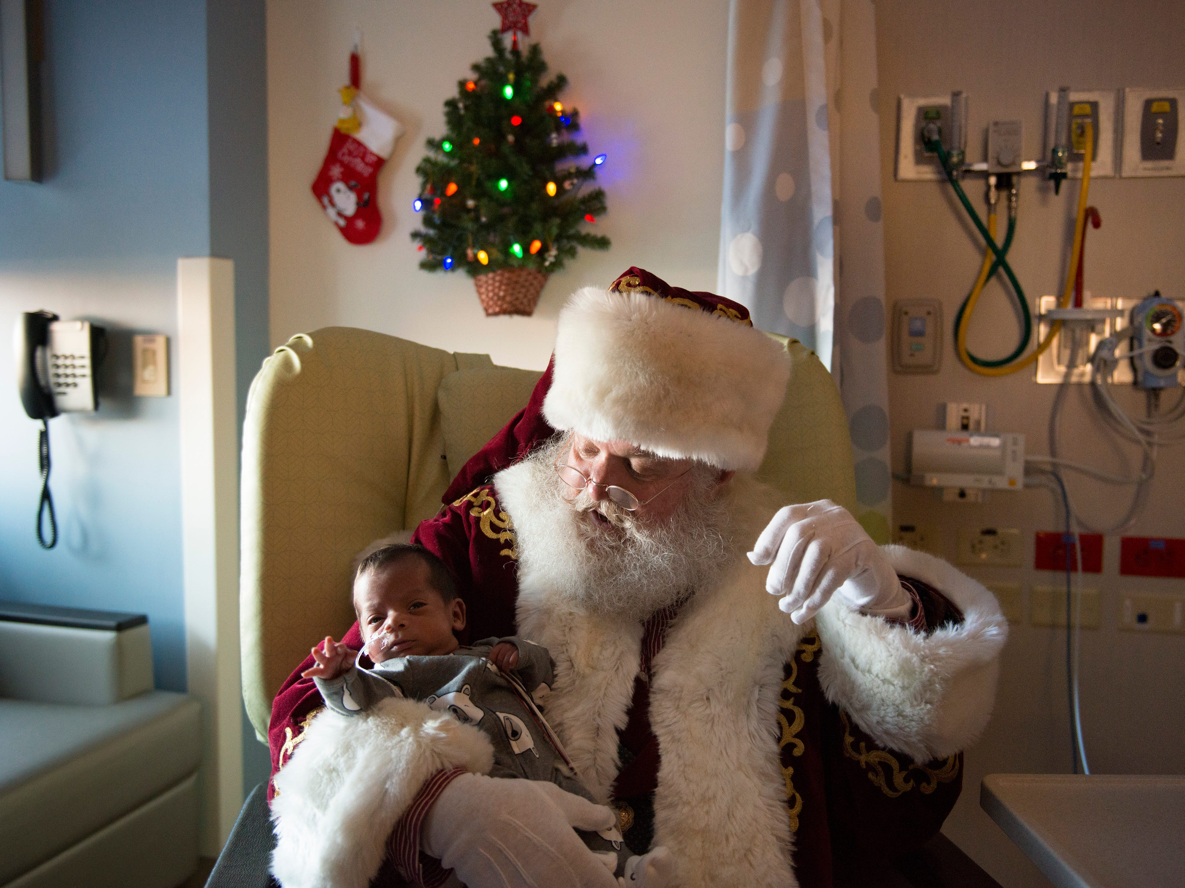 Santa Claus, portrayed by Moose Shattuck, holds Joseph Maldonado as he visits the neonatal intensive care unit at Poudre Valley Hospital on Tuesday December 18, 2018.