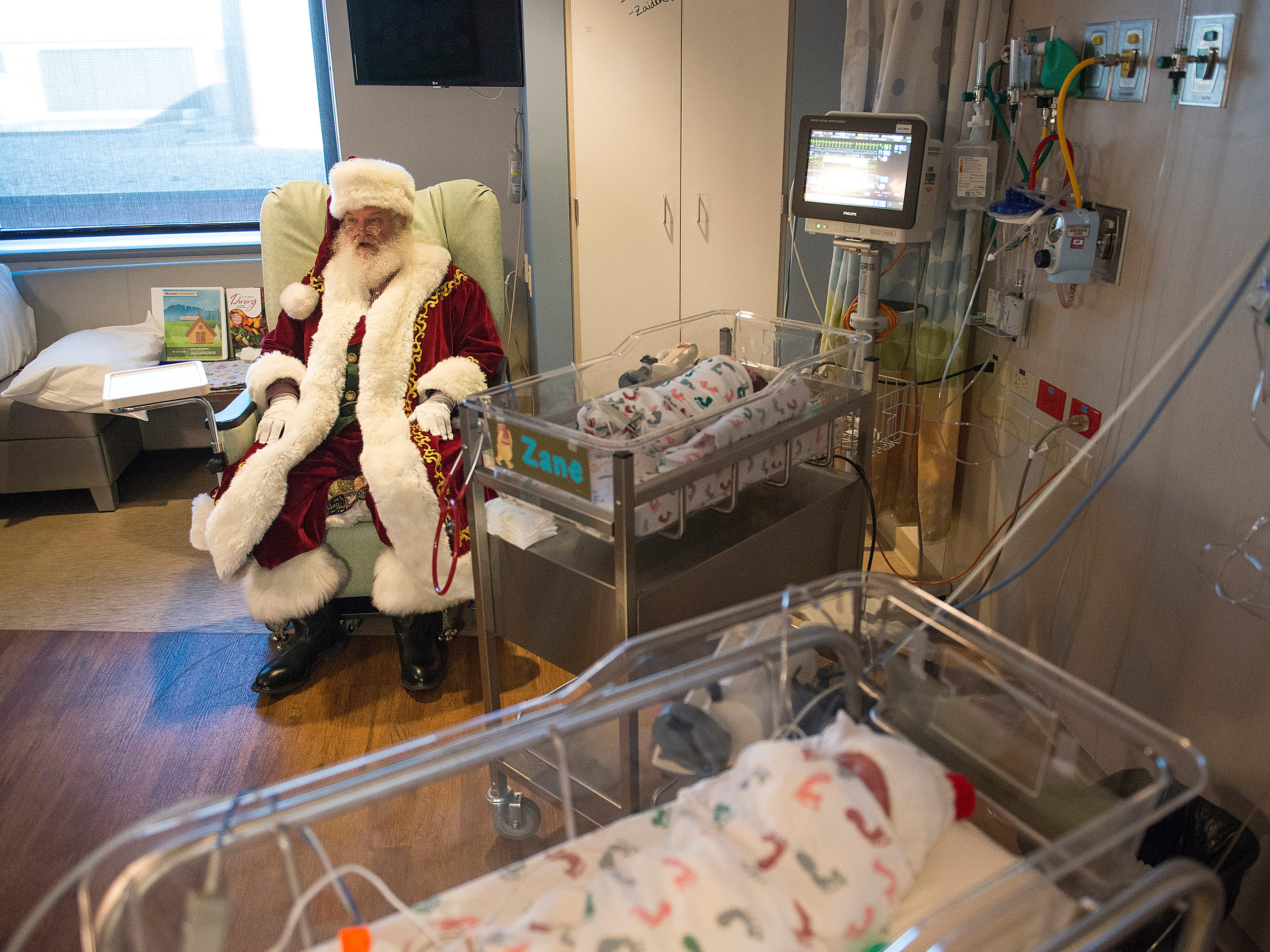 Santa Claus, portrayed by Moose Shattuck, takes a seat next to Zane and Zaiden as he visits the neonatal intensive care unit at Poudre Valley Hospital on Tuesday December 18, 2018.