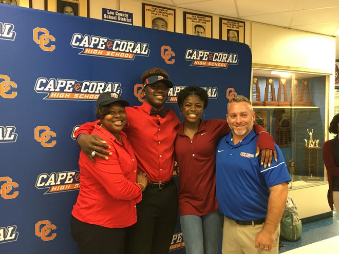 Cape Coral defensive end Tre'Shaun Clark poses with his mother, Sherrita Clark, sister N'Tayla Clark and Seahawks coach Dale More after signing with Liberty University on Wednesday, Dec. 19, 2018.