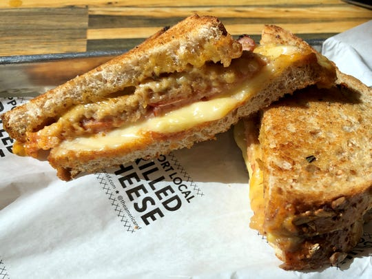 The Piglet comes with Gouda, cheddar, cured ham, caramelized apple spread, tomato, and rosemary butter on whole grain bread.