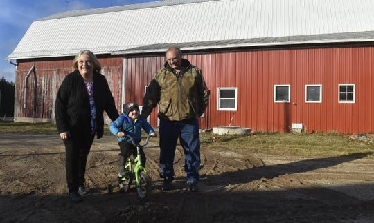 Dale and Karen Cihlar help their four-year-old grandson Case maneuver his bicycle through a muddy area on their rural southern Door County farm on Tuesday, Dec. 18, 2018. Tina M. Gohr/USA TODAY NETWORK-Wisconsin