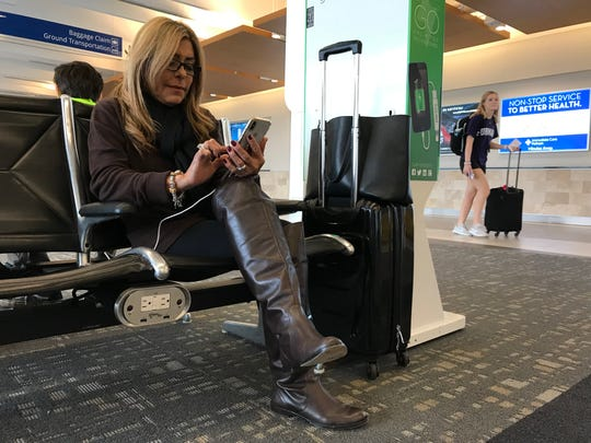 Ileana Miranda of Miami checks her phone while she waits for her 6:46 p.m. flight to Miami on Wednesday, Dec. 19, 2019. Miranda was on the airport's first direct, daily flight to Miami -- a great convenience, she said, for businesswomen such as herself.