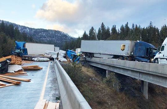 This photo provided by the Frenchtown Rural Fire District shows where five tractor-trailers crashed on icy Interstate 90 near the town of Superior in western Montana early Wednesday, Dec. 19, 2018, leading to the deaths of two drivers and injuries to two other people, including a rural firefighter who slipped and fell on an icy bridge deck. One driver jumped out of his rig to avoid oncoming traffic and went over a guardrail, falling to his death. (Mel Holtz/Frenchtown Rural Fire District via AP)