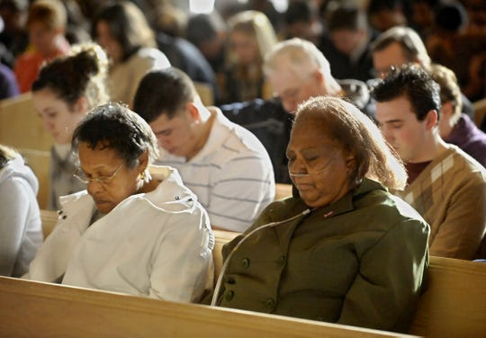 """Cleo Miles, left, and Mary Ghee bow their heads in prayer during a 2010 Martin Luther King, Jr. celebration at the University of Great Falls. Miles, now 100 years old, said church has been an important part of her life. She loves to sing, particularly """"Amazing Grace."""""""