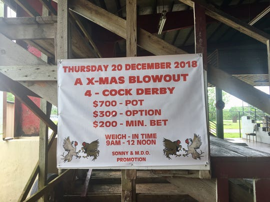 A sign detailing the Christmas cockfight at the pit in Dededo.