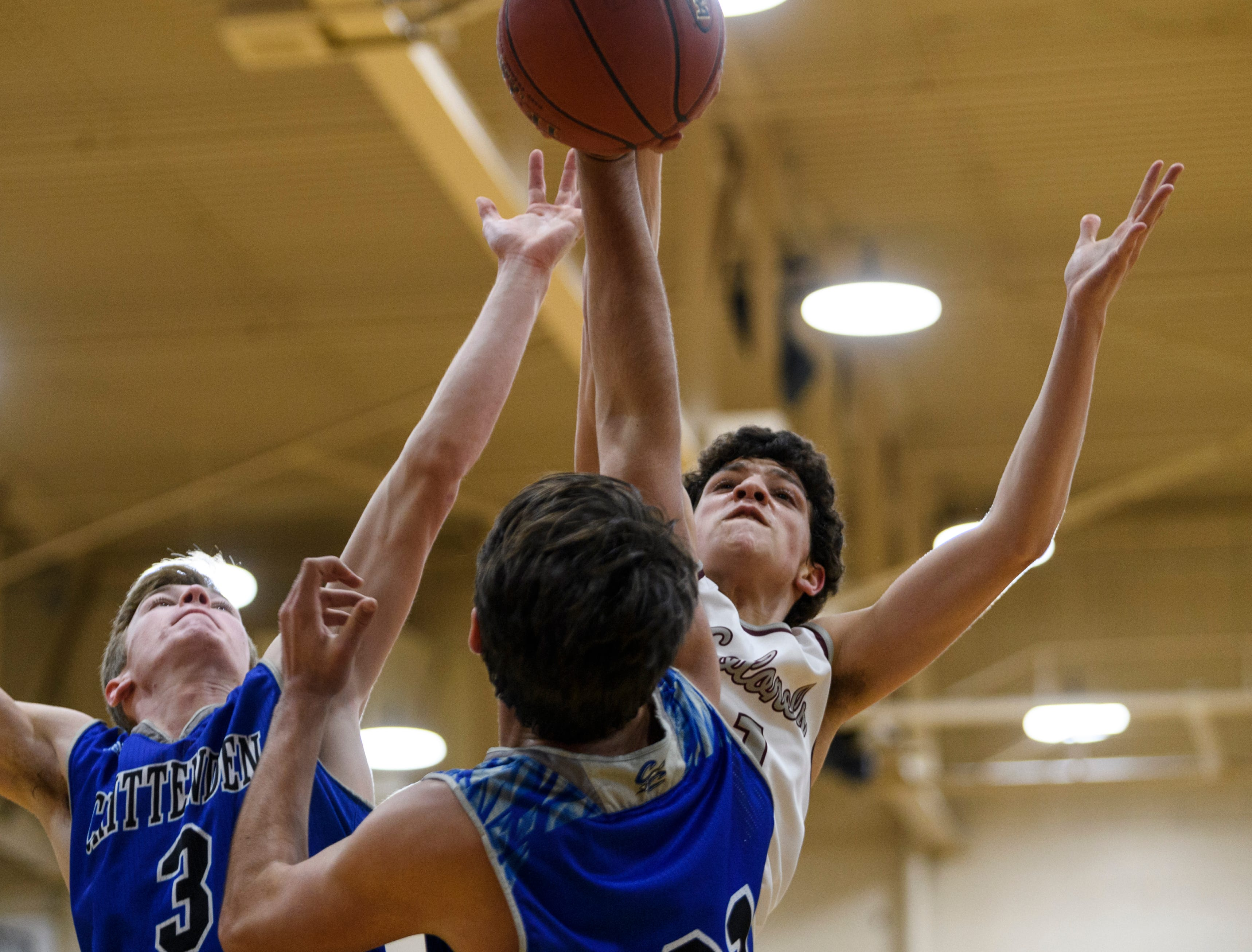 Crittenden County's Sawyer Towery (3) and Preston Turley (31) fight Henderson's Corey Stewart (1) for possession of a rebound during the first quarter at Henderson County High School in Henderson, Ky., Tuesday, Dec. 18, 2018. The Colonels defeated the Rockets 88-52.