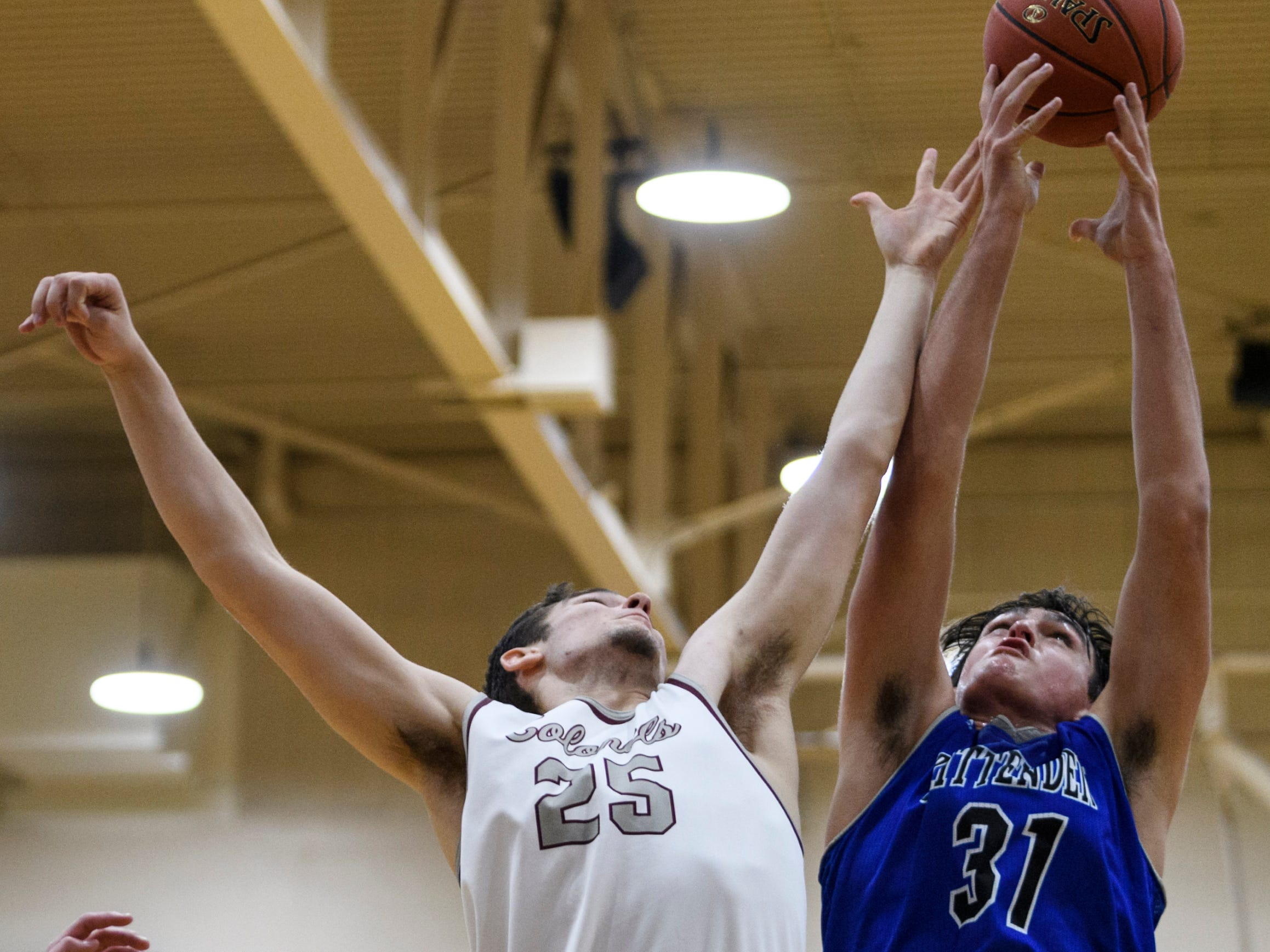 Henderson's Alec Agnew (25) and Crittenden County's Preston Turley (31) fight for the rebound during the game at Henderson County High School in Henderson, Ky., Tuesday, Dec. 18, 2018. The Colonels defeated the Rockets 88-52.