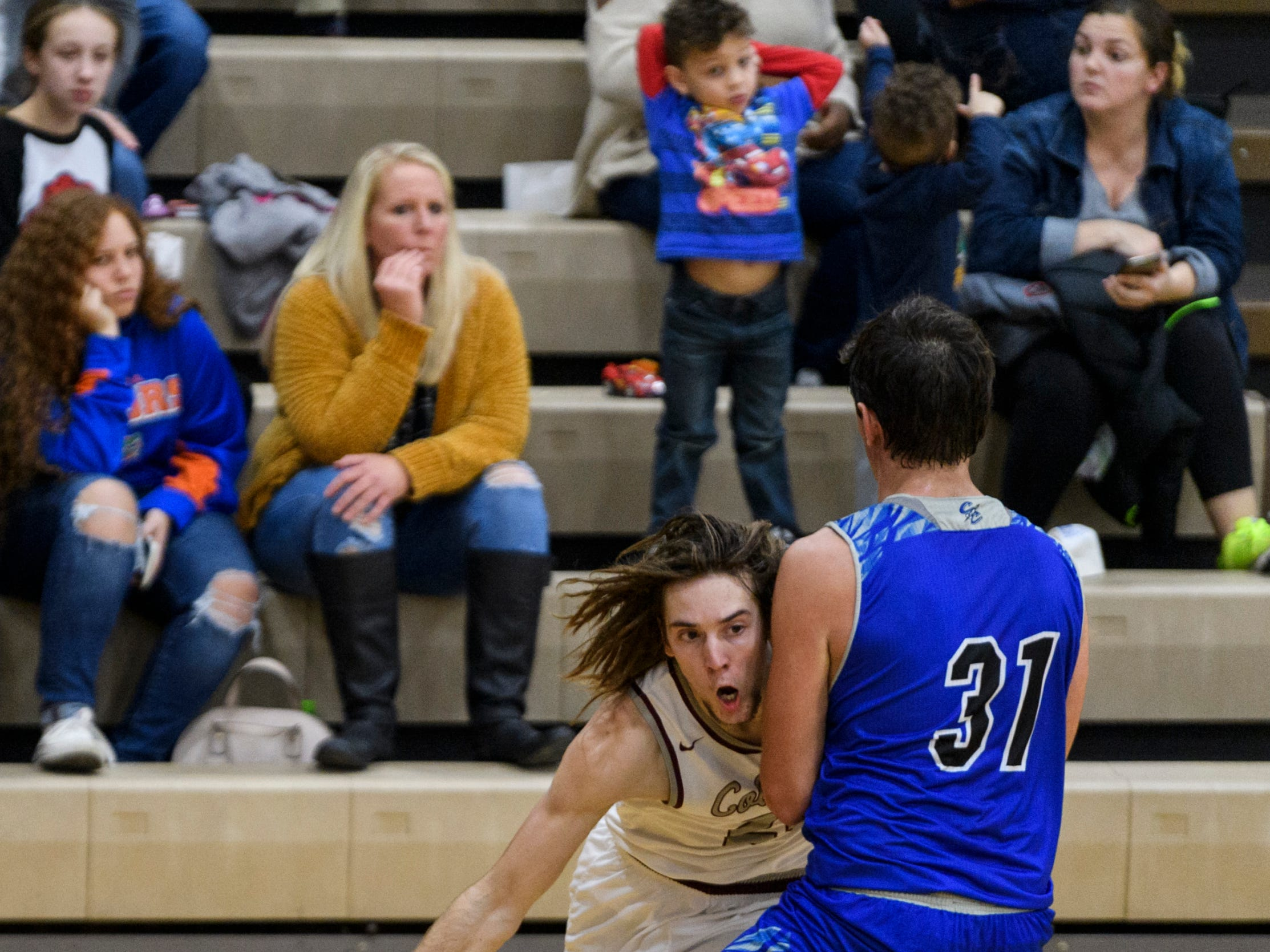 Henderson's Nick Cissell (22) advances to the net as Crittenden County's Preston Turley (31) guards him during the second quarter Henderson County High School in Henderson, Ky., Tuesday, Dec. 18, 2018. The Colonels defeated the Rockets 88-52.