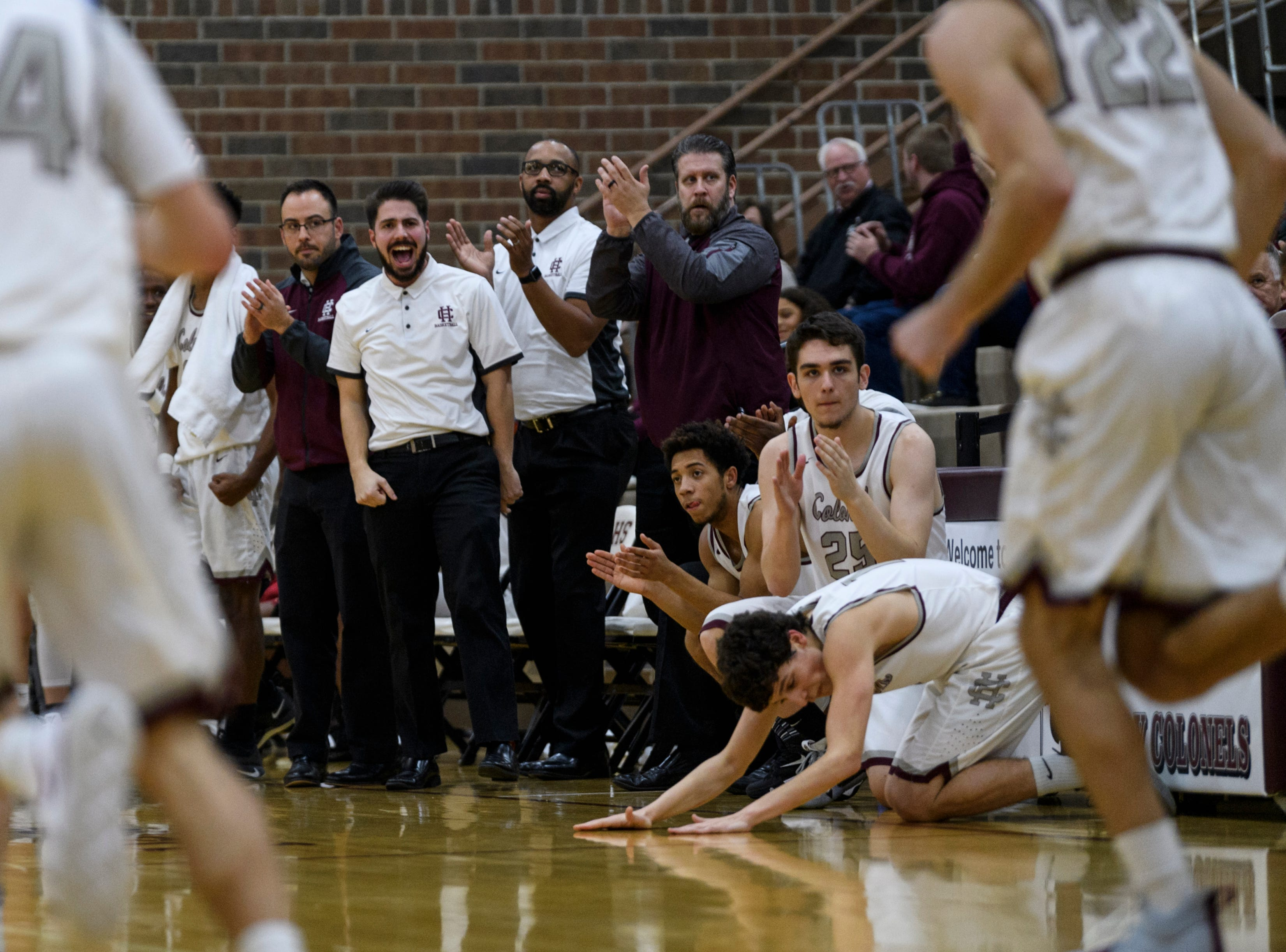 The Henderson County Colonels bench reacts to Henderson's Nick Cissell (22) making a three-pointer at the end of the first quarter against the Crittenden County Rockets at Henderson County High School in Henderson, Ky., Tuesday, Dec. 18, 2018. The Colonels defeated the Rockets 88-52.