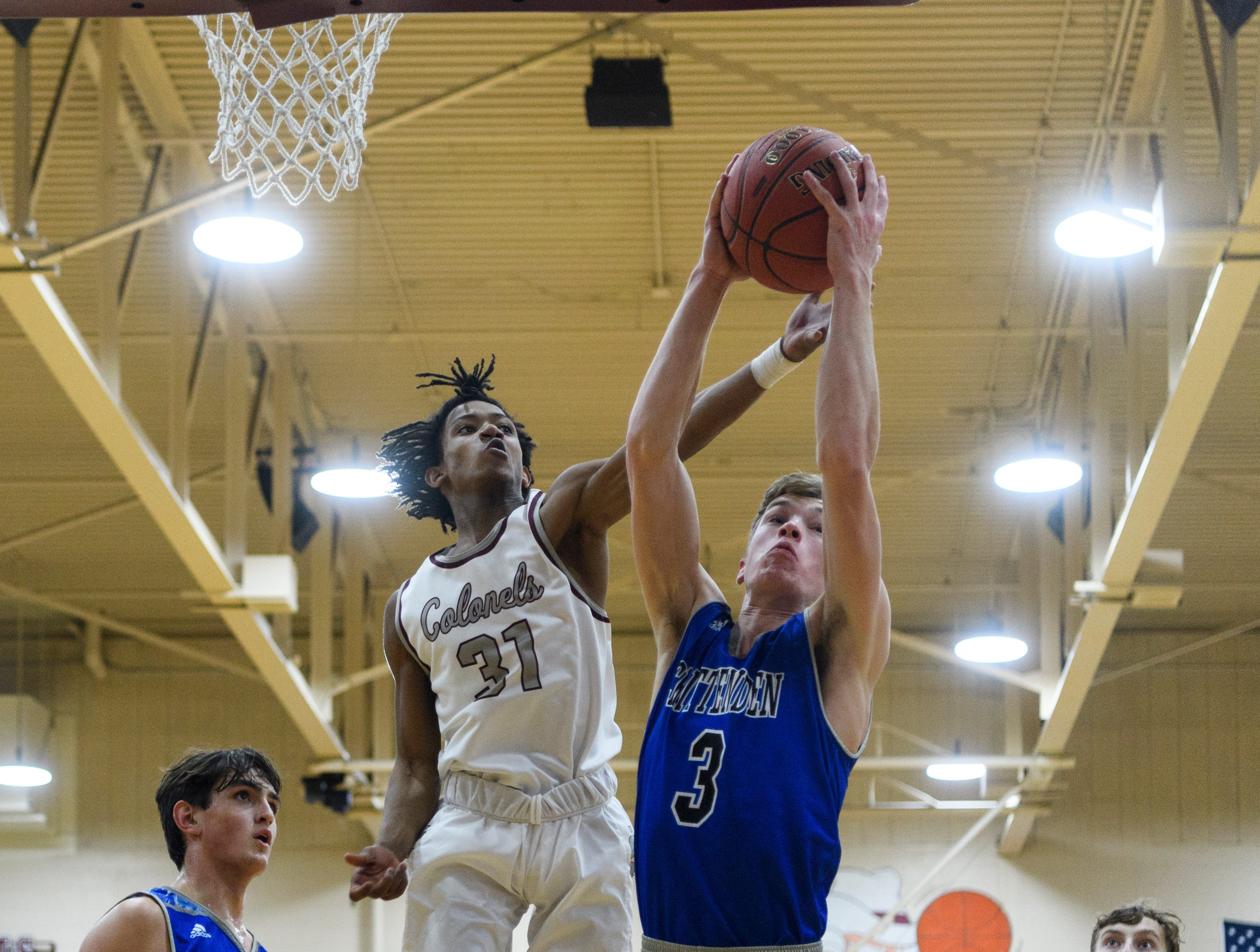 Henderson's Zac Green (31) attempts to take the rebound from Crittenden County's Sawyer Towery during the first quarter at Henderson County High School in Henderson, Ky., Tuesday, Dec. 18, 2018. The Colonels defeated the Rockets 88-52.
