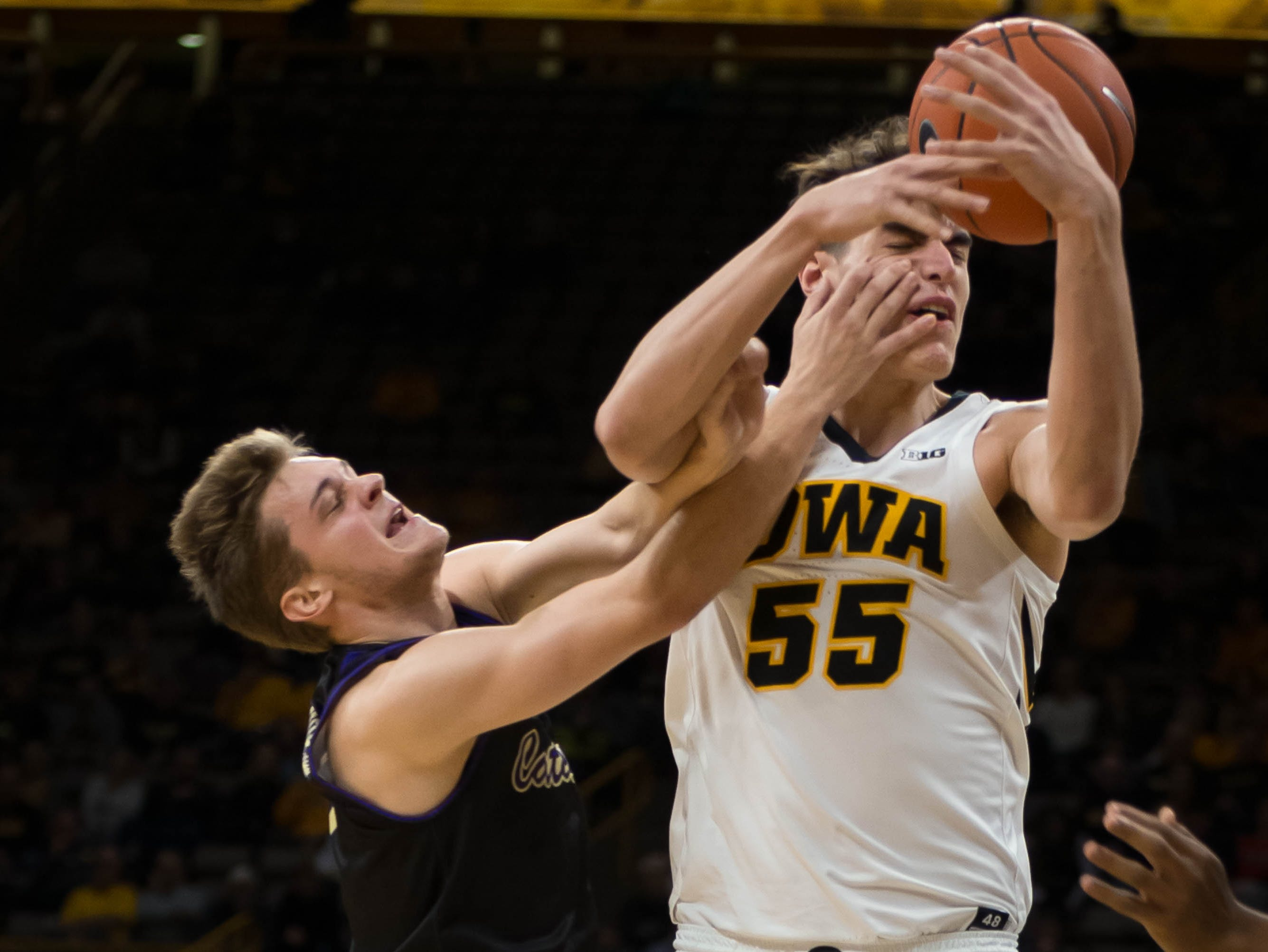 Western Carolina sophomore guard Matt Halvorsen (2) grabs at Iowa sophomore forward Luka Garza (55) in the first half at Carver Hawkeye Arena in Iowa City on Tuesday, Dec. 18, 2018.