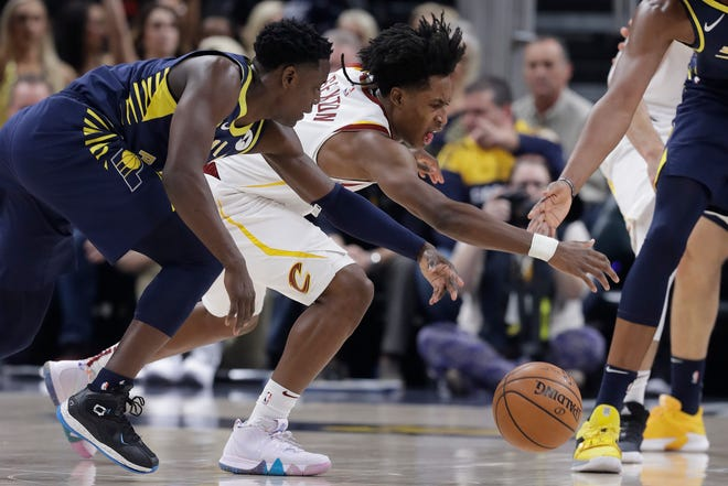 Indiana Pacers' Darren Collison, left, and and Cleveland Cavaliers' Collin Sexton battle for a loose ball during the first half of an NBA basketball game, Tuesday, Dec. 18, 2018, in Indianapolis.