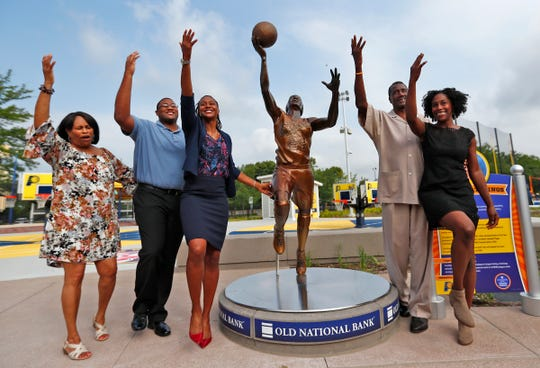 Basketball star Tamika Catchings, third from left, strikes a pose with her family, including her mom Wanda Catchings, her husband Parnell Smith, her dad Harvey Catchings, and her sister Tauja Catchings, after the unveiling ceremony for the new bronze statues of iconic Indiana sports legends, Tuesday, July 24, 2018, in the Riley Children's Health Sports Legends Experience area at the Children's Museum of Indianapolis.  Catchings is one of the statues.  This is her first statue.