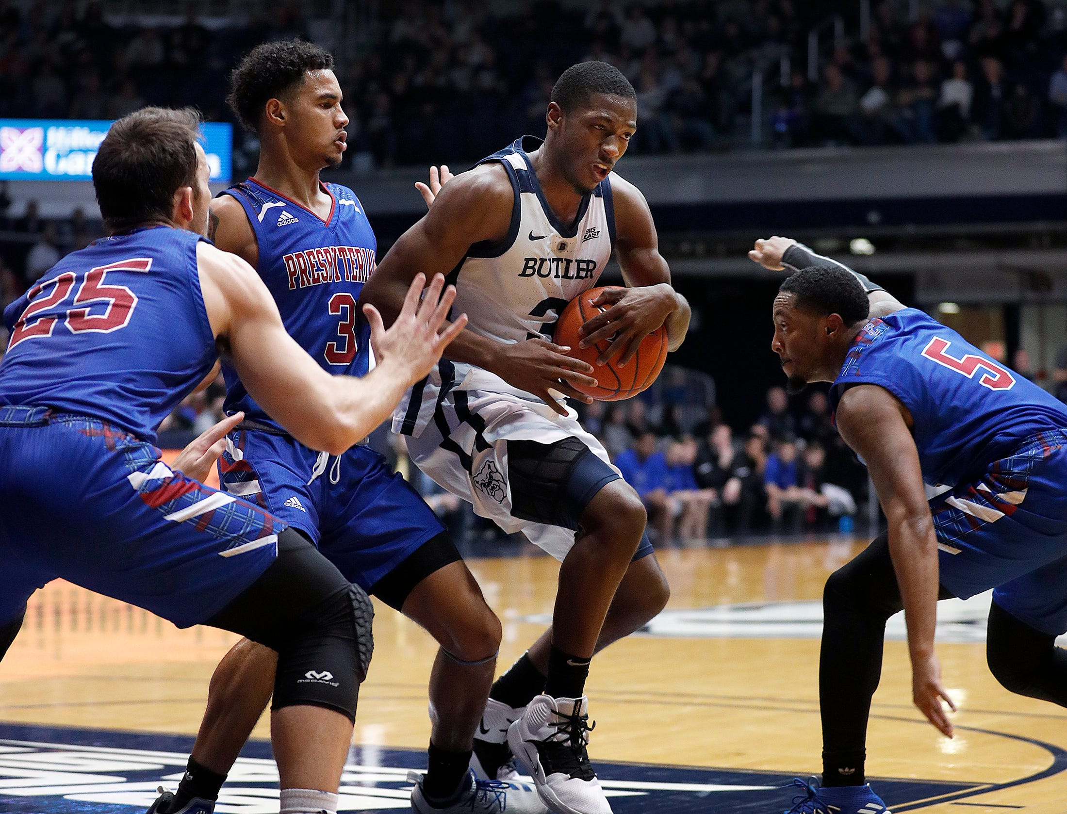 Butler Bulldogs guard Kamar Baldwin (3) is defended by Presbyterian Blue Hose guard Romeo Crouch (3) and Davon Bell (5) in the second half of their game at Hinkle Fieldhouse on Monday, Dec. 18, 2018.