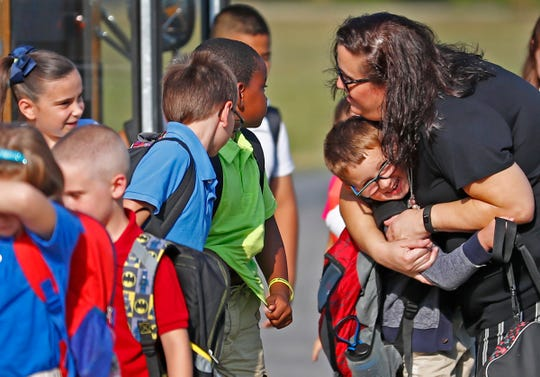 Librarian Becky Schmidt hugs kids as the Perry Township students arrive for the first day of school at Southport Elementary School, Wednesday, July 25, 2018.