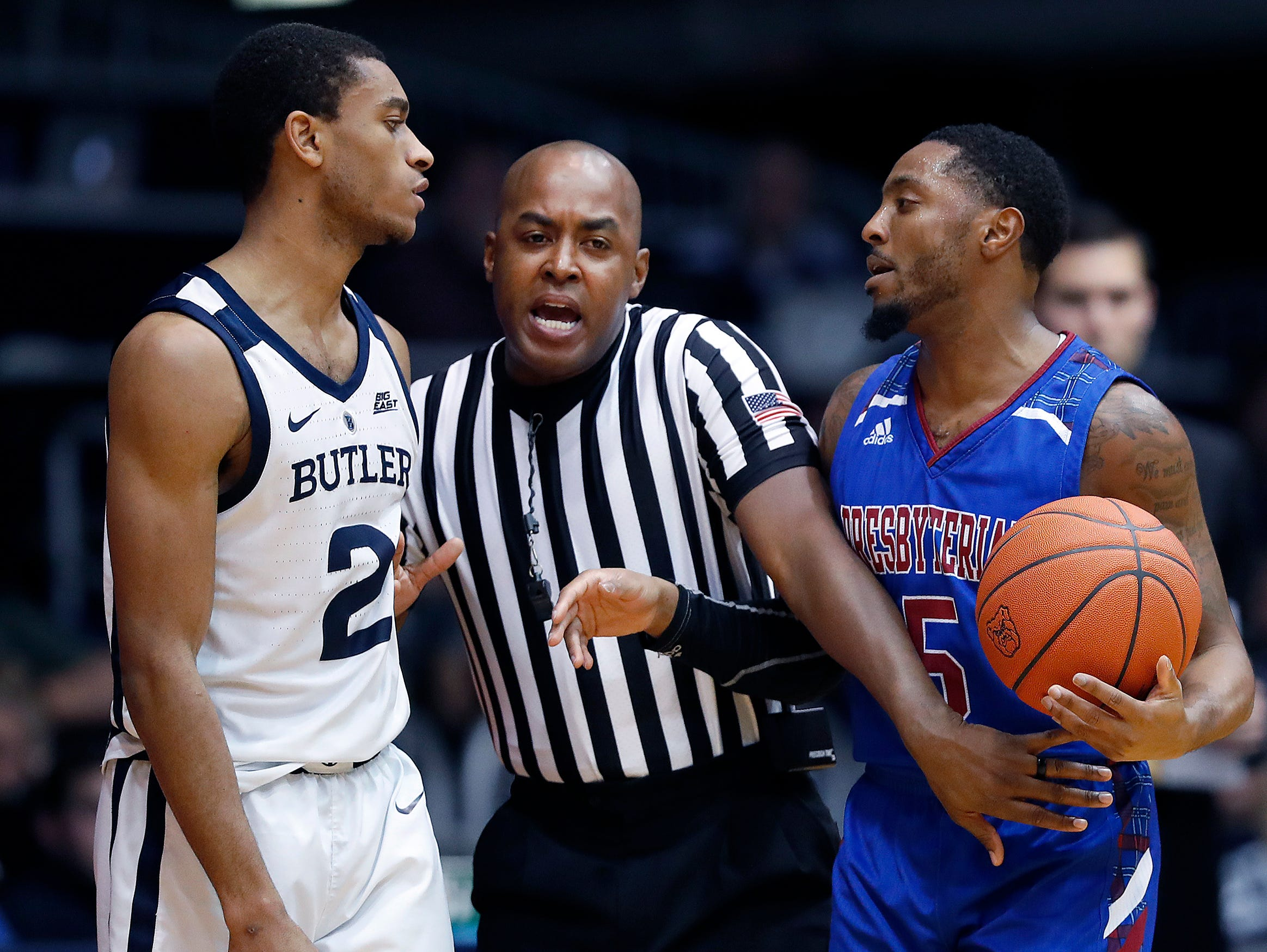 Butler Bulldogs guard Aaron Thompson (2) and Presbyterian Blue Hose guard Davon Bell (5) are separated by official Evon Burroughs in the second half of their game at Hinkle Fieldhouse on Monday, Dec. 18, 2018.
