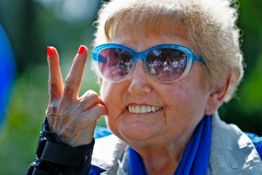 "Holocaust survivor Eva Kor gives the peace sign and smiles during the planting of the Eva Kor Peace Garden at Newfields, Monday, Sept. 17, 2018.  Students viewed the documentary ""Eva,"" about Holocaust survivor Eva Kor, and then helped in the planting of the Peace Garden.  Kor also spoke with the students, asking them to think of one thing to make the world better."