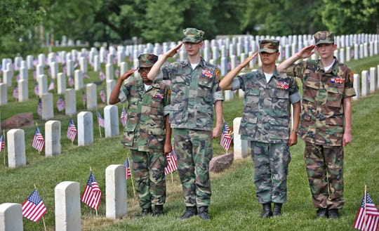 Central Indiana Young Marines members Pfc. Jazmine Rowie, left, Sgt. Matthew Cummins, Sgt. Charlie Clark and Cpl. Sam McCullough salute during a Memorial Day observance at Crown Hill Cemetery in 2018.