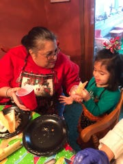 Dolores Quiroz helping her granddaughter, Murphy, wrap a tamale during a tamalada on Jan. 8 in Indianapolis.
