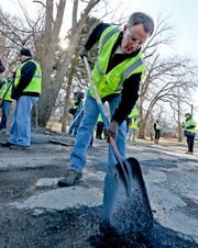 Mayor Joe Hogsett pitches in to fill pot holes on the first day of a 4-day pothole blitz.