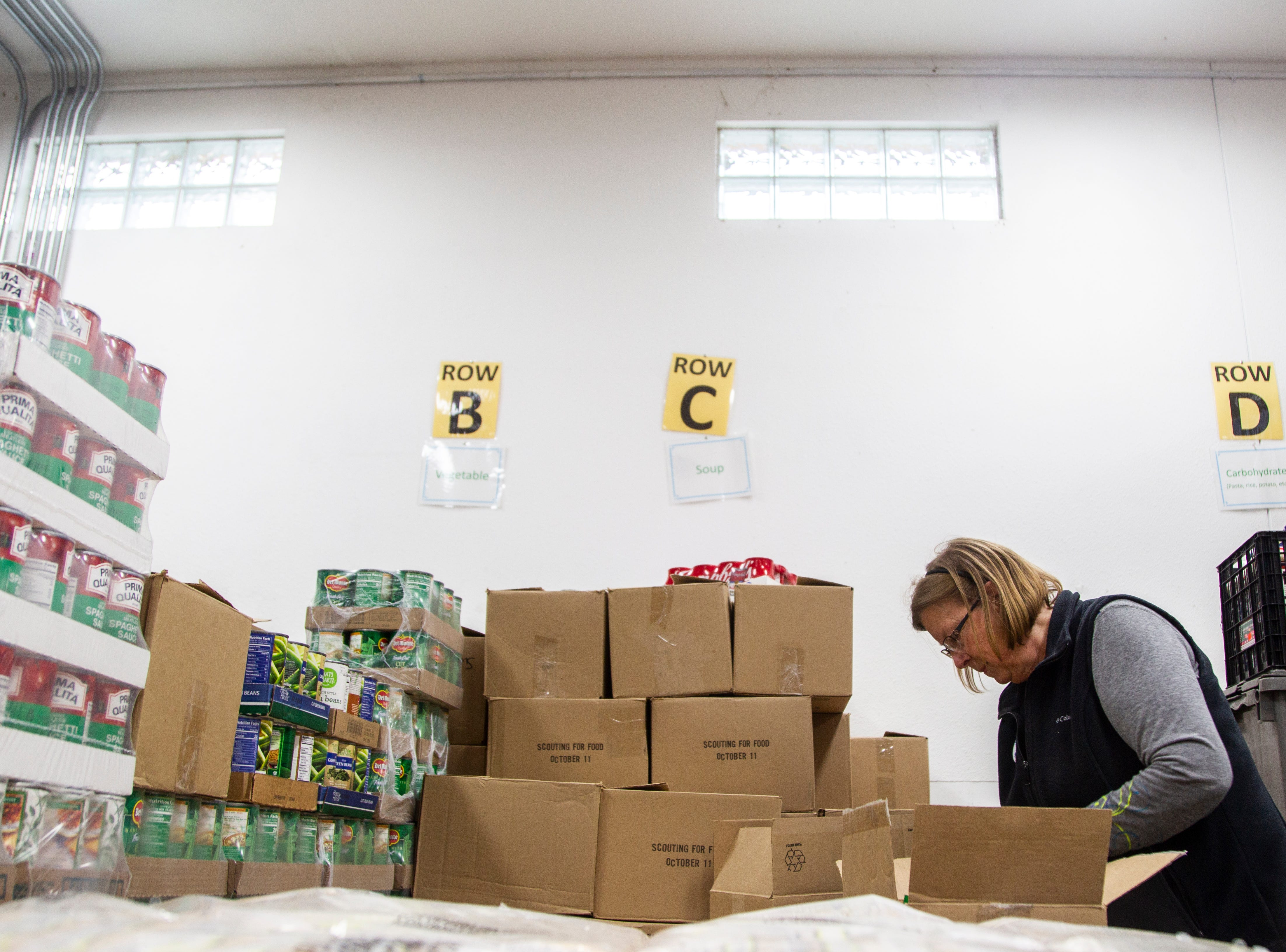 "Crisis Center volunteer Shari Ellis sorts soup items during a ""Project Holiday"" event on Wednesday, Dec. 19, 2018, at the Crisis Center in Iowa City. Ellis has been volunteering at the center since 2006."