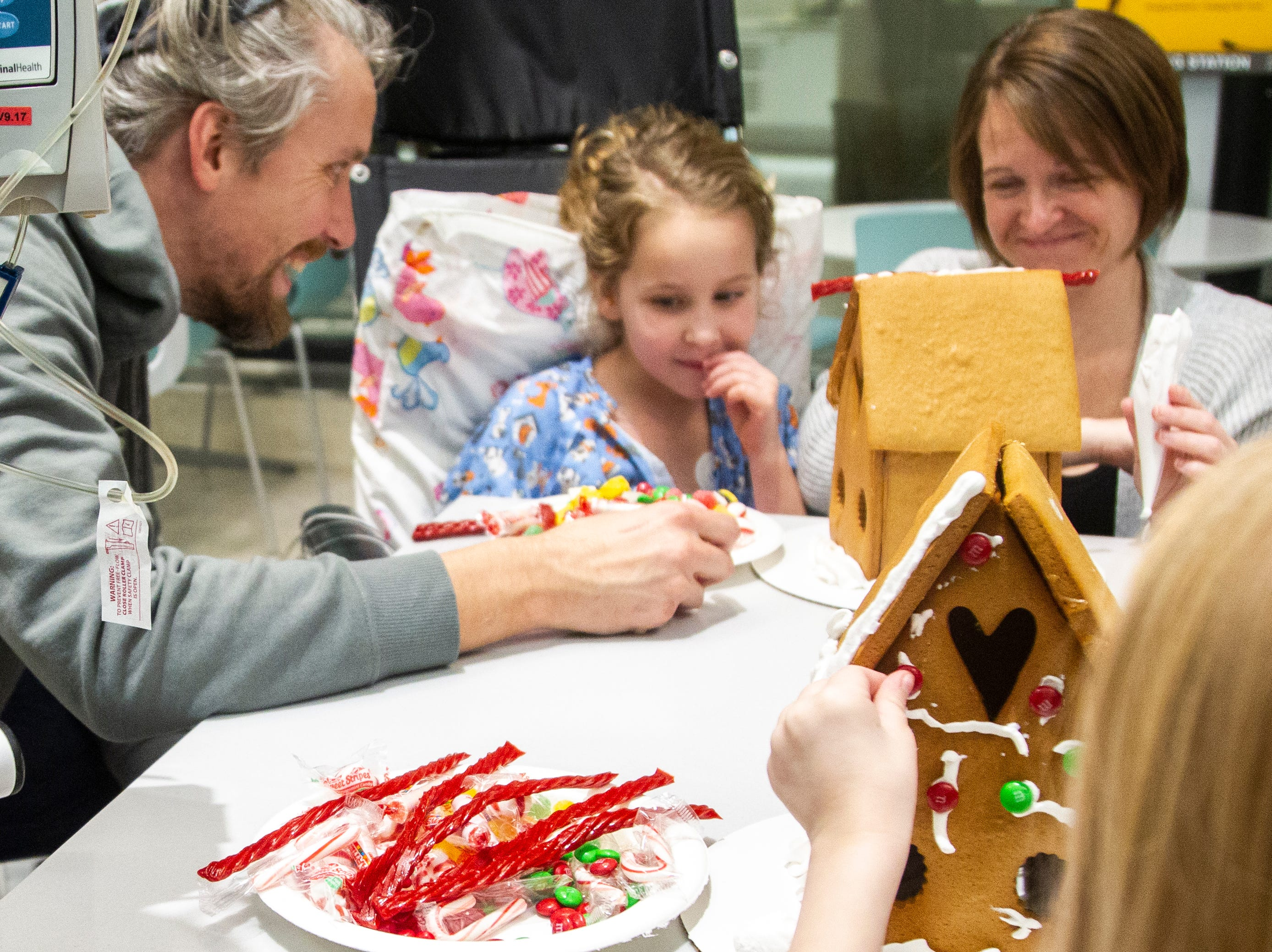 Ava Kruse (far right) places candy on a gingerbread hosue while John, Wrenlie and Kristie Bixler decorate a house at an event on Tuesday, Dec. 18, 2018, at the Stead Family Children's Hospital in Iowa City.