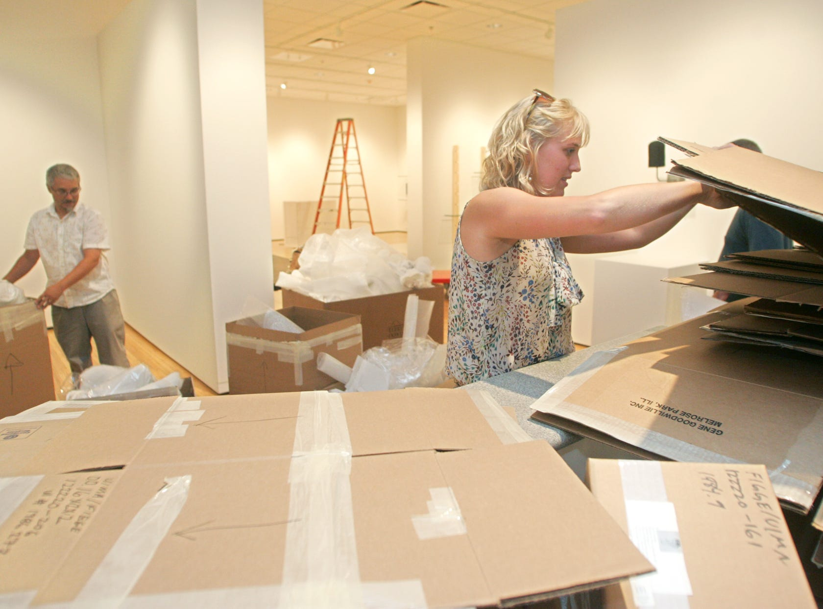 PC photo by Dan Williamson. 8-12-09. University of Iowa Museum of Art Prepator (cq) Steve Erickson, left, and Marketing and Media Manager Maggie Anderson sort through packing material after helping to set up artwork for the new UIMA @ IMU art gallery in the Richey Ballroom at the Iowa Memorial Union on Wednesday, Aug. 12, 2009, in Iowa City.
