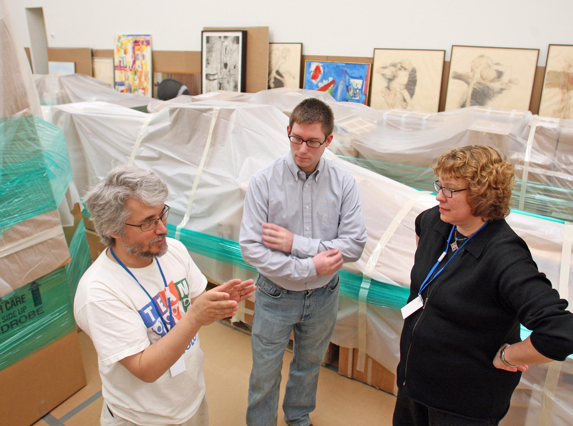 Steven Erickson, left, Nathan Popp and Kathleen Edwards, all with the University of Iowa Museum of Art, stand  amid items from the UI art collection on the fourth floor of Figge Art Museum in Davenport. The museum is providing storage and display space for the art, which was displaced when the museum in Iowa City flooded last summer.
