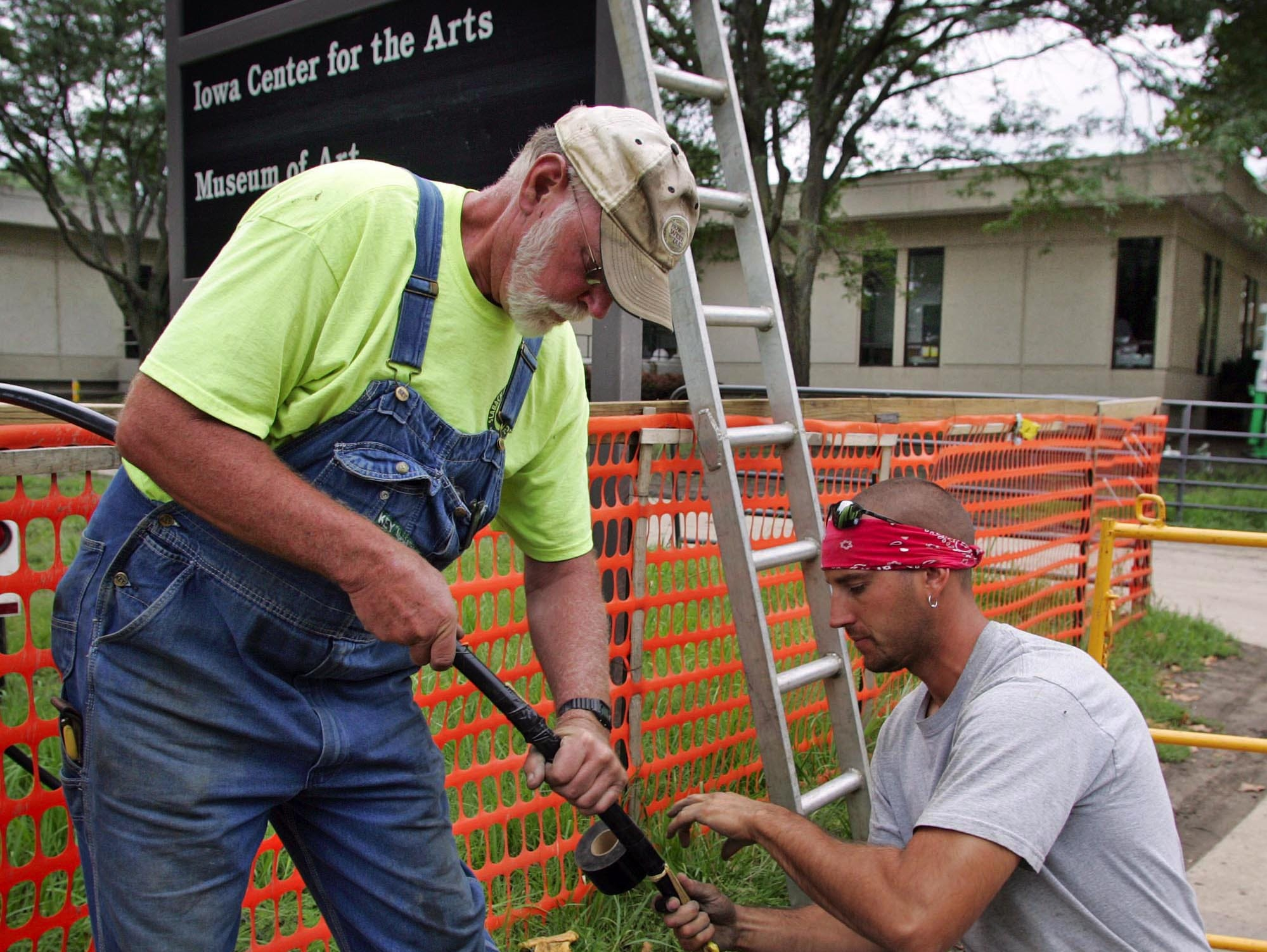 Lewis Payne, left and Tyler Hershberger, with Slabach Construction of Kalona, work with fiber optic cable outside the University of Iowa Museum of Art, background, as flood repairs continue on Wednesday. Officials said that music students will use the the building for practice space.