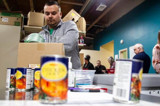 """MidWestOne Bank volunteer Derek Logas sorts food during a """"Project Holiday"""" event on Wednesday, Dec. 19, 2018, at the Crisis Center in Iowa City. The food bank, now called CommUnity Food Bank, receives many donations during the winter. This summer, they are reporting a sudden decrease in donations."""
