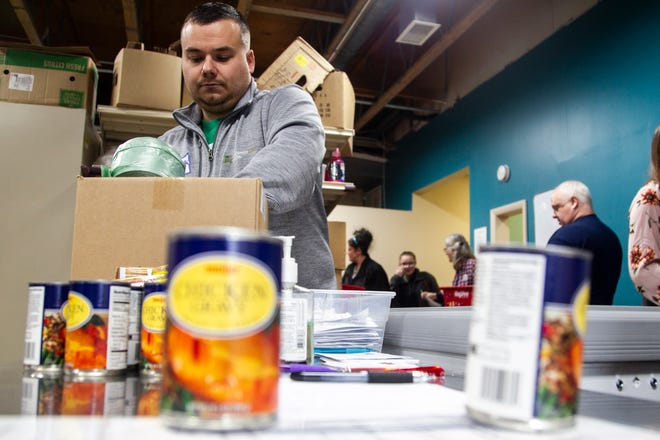 "MidWestOne Bank volunteer Derek Logas sorts food during a ""Project Holiday"" event on Wednesday, Dec. 19, 2018, at the Crisis Center in Iowa City. The food bank, now called CommUnity Food Bank, receives many donations during the winter. This summer, they are reporting a sudden decrease in donations."