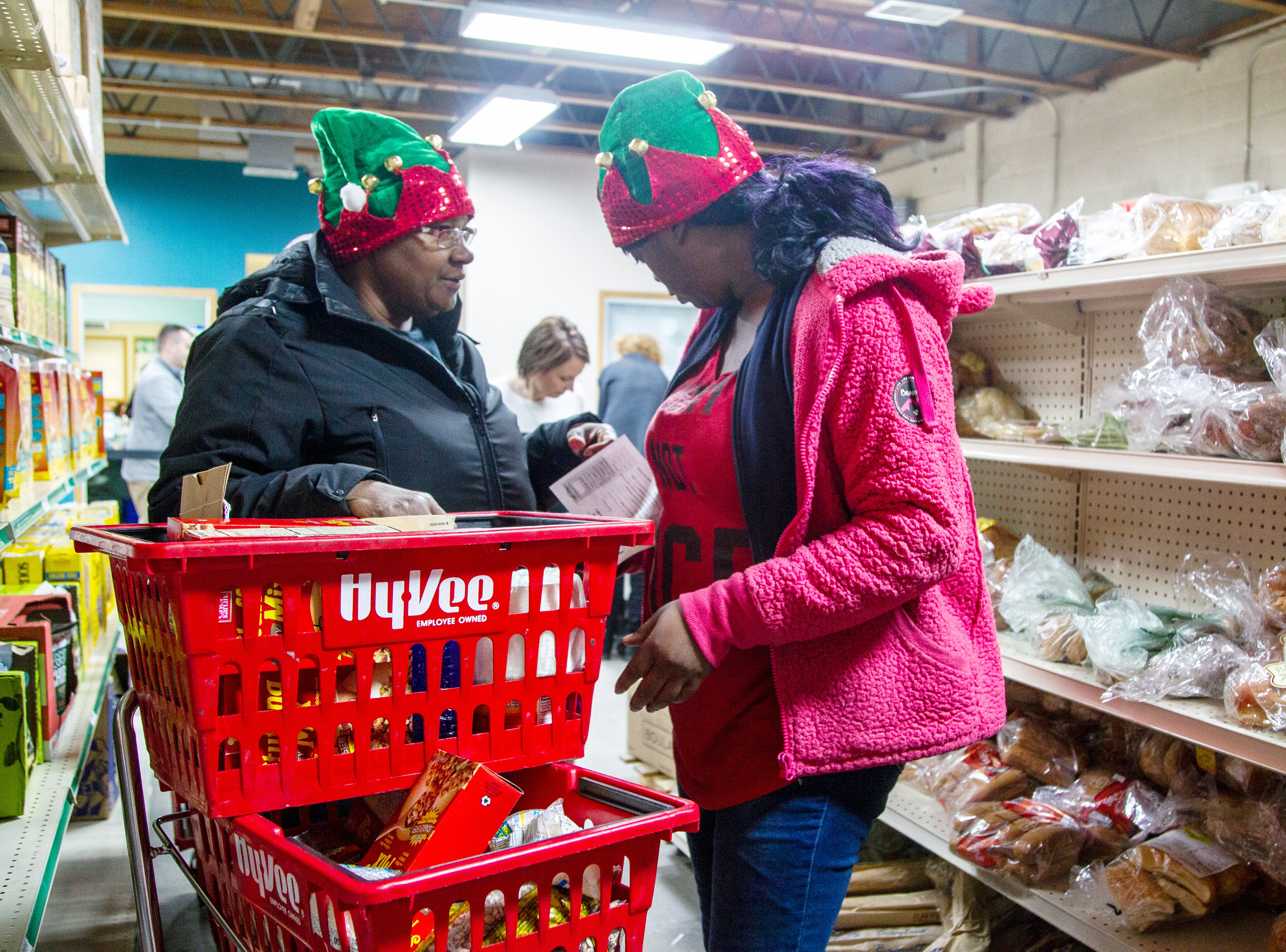 "Gladys Watkins, left, and Martina Smith, both of Iowa City pick out food items during a ""Project Holiday"" event on Wednesday, Dec. 19, 2018, at the Crisis Center in Iowa City. The meal distribution service runs from Dec. 17-21."