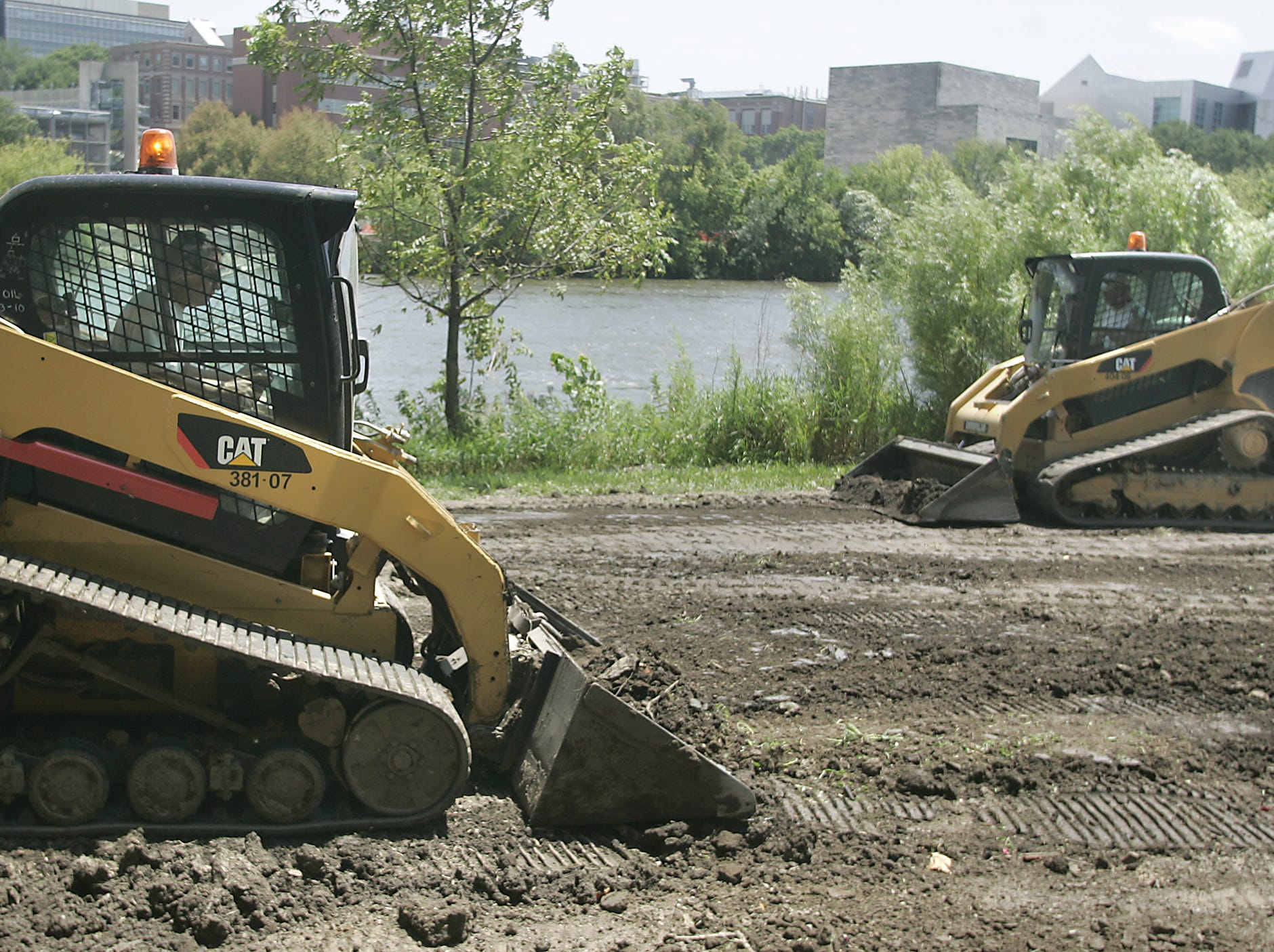 Bobcats excavate the ground around the sidewalk project between the flooded UI Art Museum and Art School, along the Iowa river, Thursday, July 22, 2010, in Iowa City, Iowa.