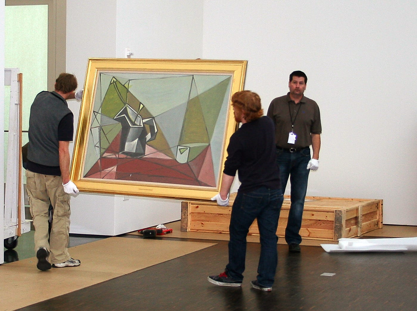 "Special to the Press-Citizen. March 2009. Art movers carry Pablo Picasso's ""Flower Vase on a Table,"" 1942, oil on canvas, 38 1/16"" x 51 1/4"". University of Iowa Museum of Art, gift of Owen and Leone Elliot, 1968.39, through the Figge galleries on Tuesday, March 17, 2009. Most of the works in the ""A Legacy for Iowa..."" exhibition were moved into the Figge that day."