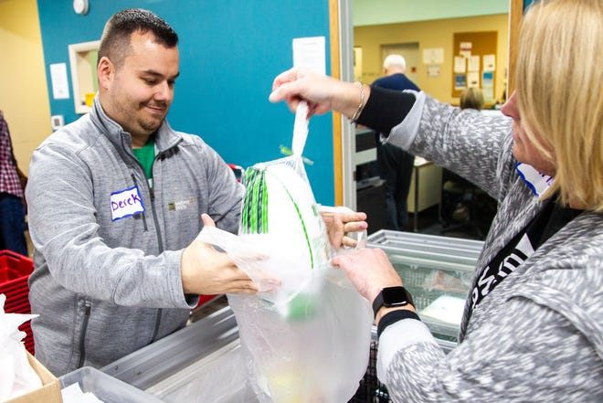 "MidWestOne Bank volunteer Derek Logas holds a bag open for fellow volunteer Christy Fehlberg during a ""Project Holiday"" event on Wednesday, Dec. 19, 2018, at the Crisis Center in Iowa City."