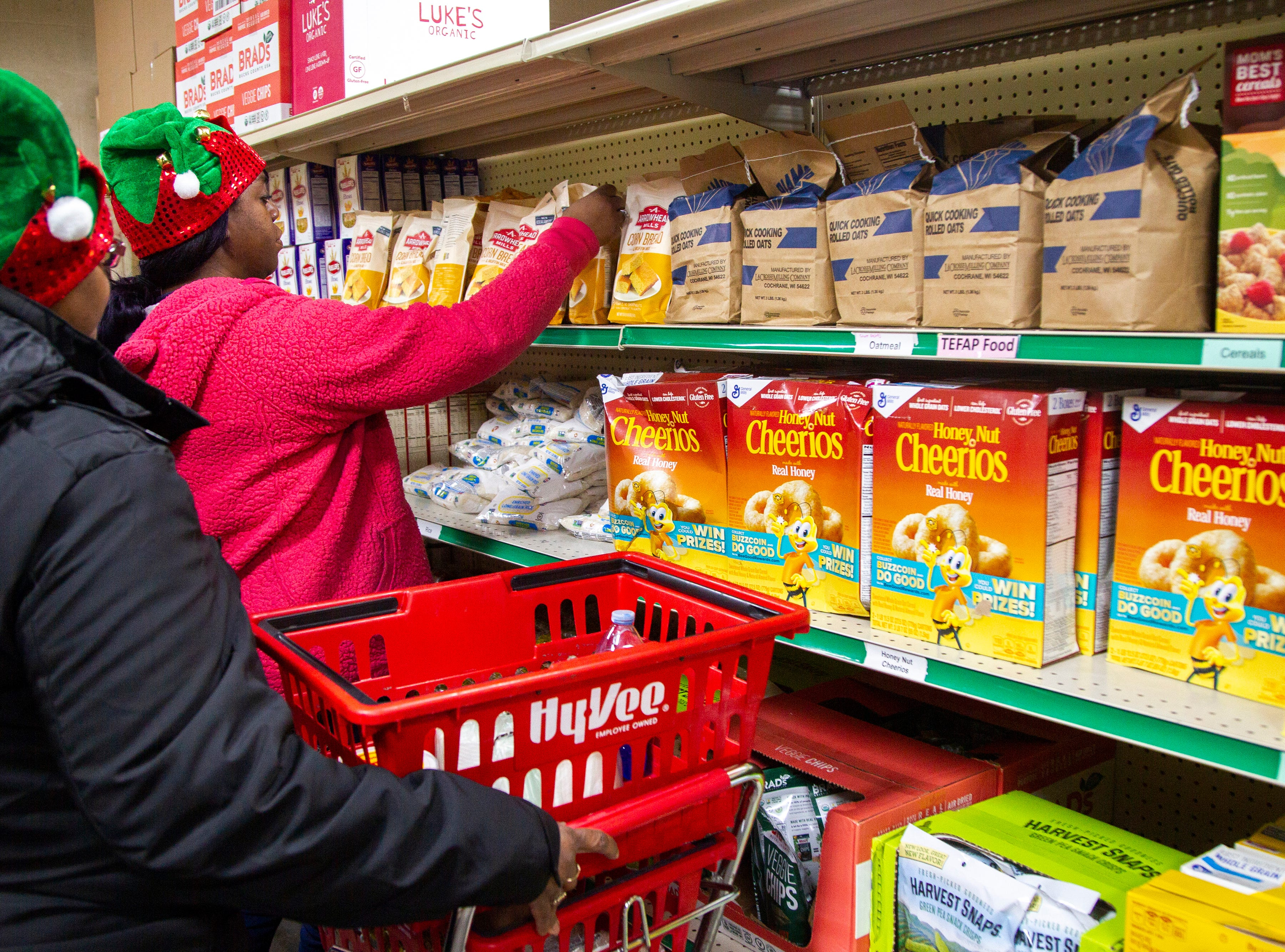 "Gladys Watkins, left, and Martina Smith, both of Iowa City pick out food items during a ""Project Holiday"" event on Wednesday, Dec. 19, 2018, at the Crisis Center in Iowa City. In 2017 more than 5,000 people received a meal through the project."