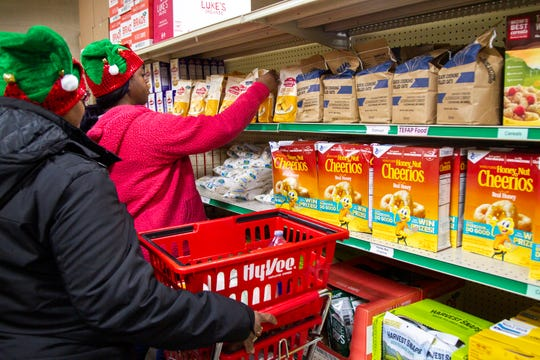 """Gladys Watkins, left, and Martina Smith, both of Iowa City pick out food items during a """"Project Holiday"""" event on Wednesday, Dec. 19, 2018, at the Crisis Center in Iowa City. In 2017 more than 5,000 people received a meal through the project."""
