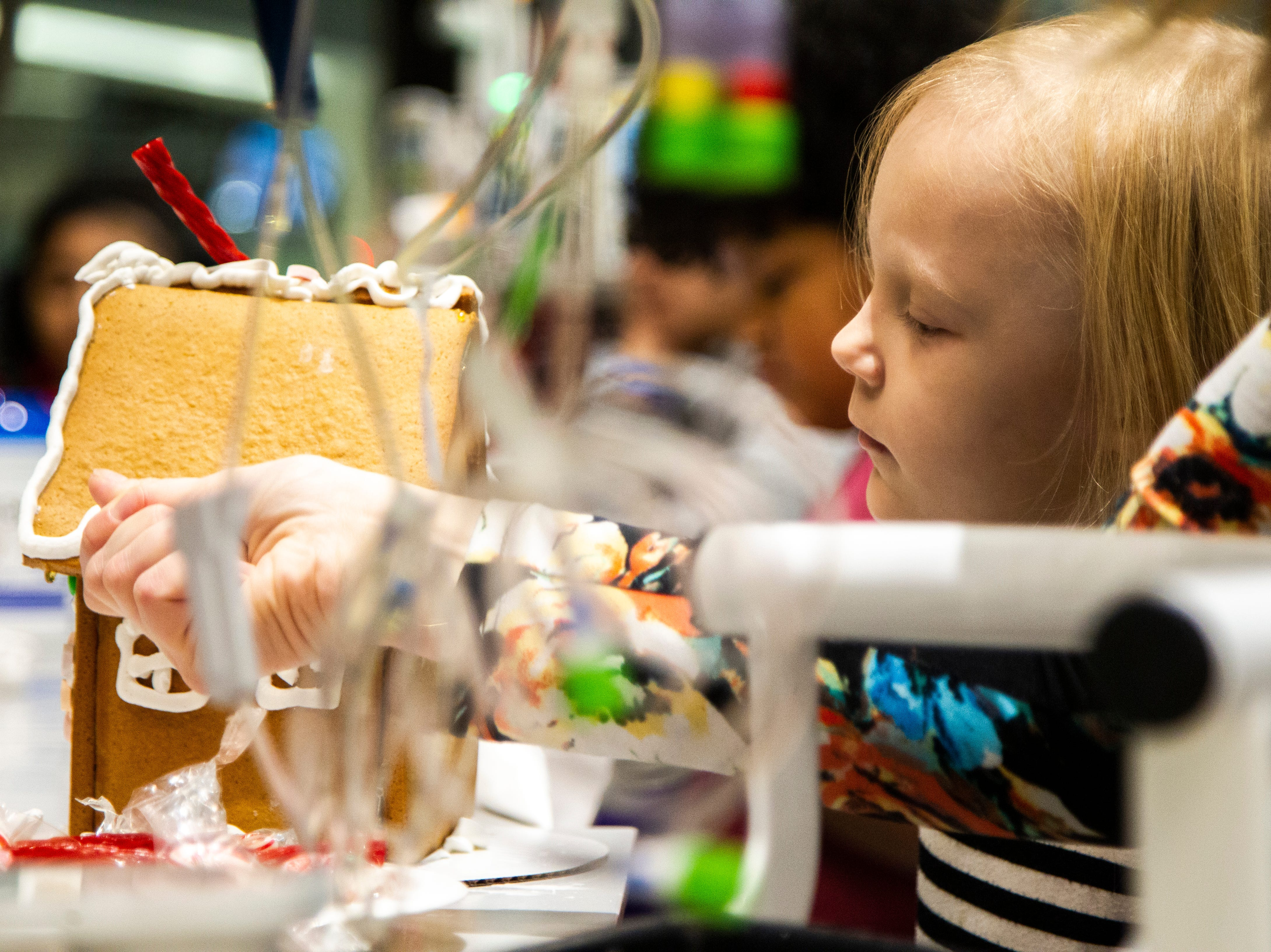 Shelby Kruse helps her daughter Ava while they decorate a gingerbread house together at an event on Tuesday, Dec. 18, 2018, at the Stead Family Children's Hospital in Iowa City.