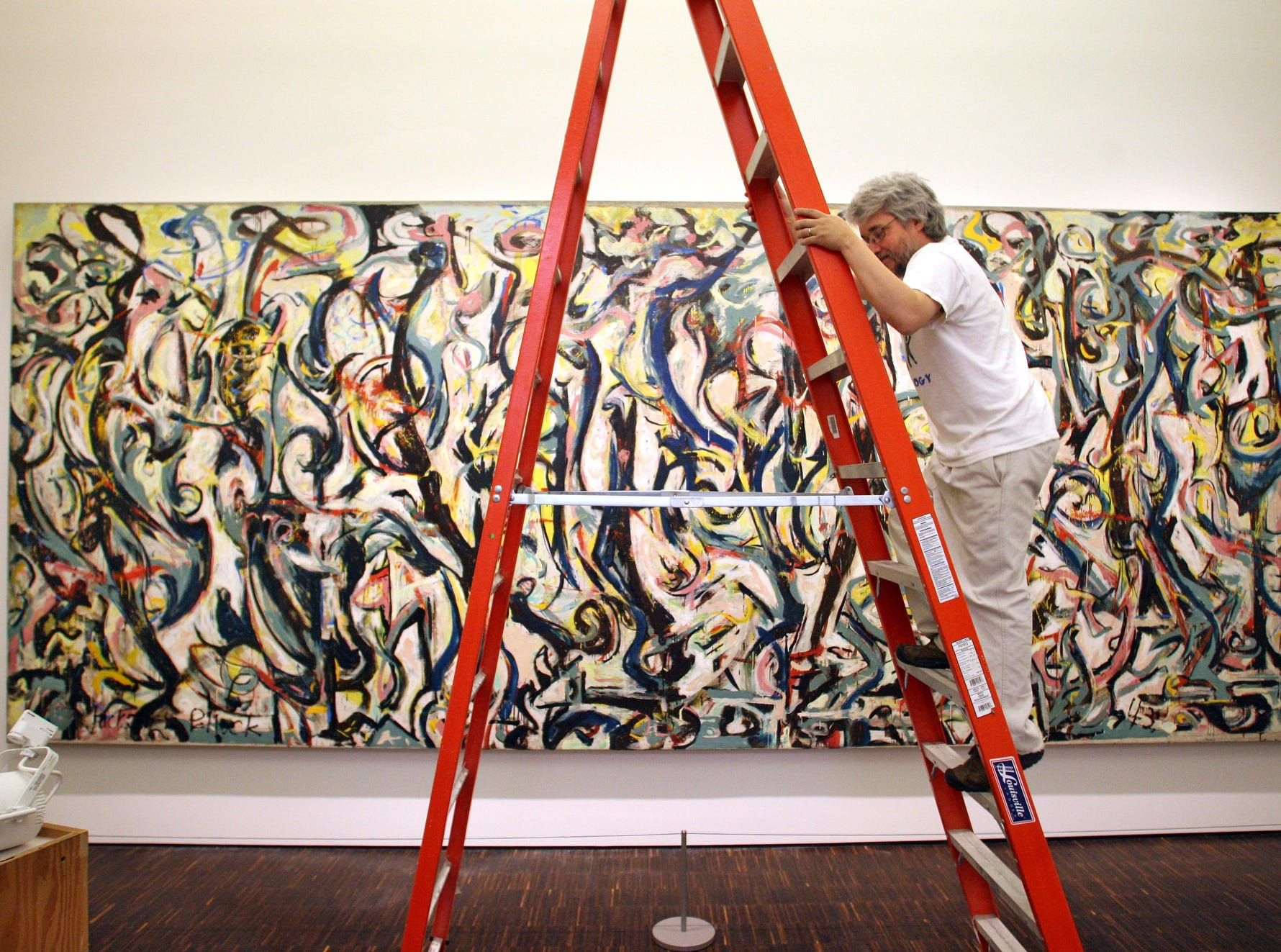 "Steven Erickson, with the UI Museum of Art, climbs a ladder at Figge Art Museum in Davenport to adjust a light aimed at ""Mural"", by Jackson Pollock, part of the University's collection being displayed at the Figge."