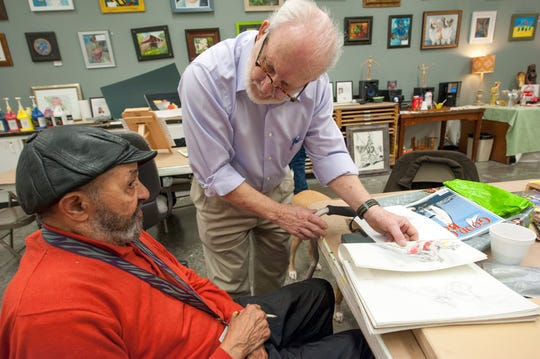 During a VSA Mississippi-sponsored Community Art Group class instructor Tom Harmon, center, talks with artist Chuck Roberts, left, of Ridgeland, about a figure he's sketched numerous times but with different interpretations. An exhibit of work created by the group is hanging at the Arts Center through Jan. 10, 2019. Harmon is the executive director of VSA Mississippi. Tuesday, Dec. 18, 2018.