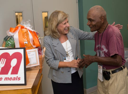 "CAC Office on Aging Director Susan Long congratulates national Meals on Wheels volunteer award winner Glenn ""Lefty"" Miller during a reception in his honor Aug. 29, 2014, at the Mobile Meals kitchen."