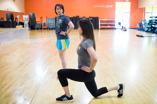 Alcoa Gold's Gym fitness manager Deonna Walker leads News Sentinel reporter Maggie Jones in a set of reverse lunges.