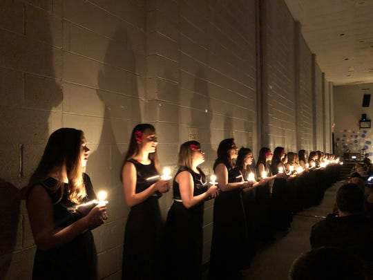 """Halls High Concert Choir lined the sides of the auditorium, lit candles and sang traditional numbers such as """"Run, Rudolph, Run"""" and """"Have Yourself a Merry Little Christmas."""""""
