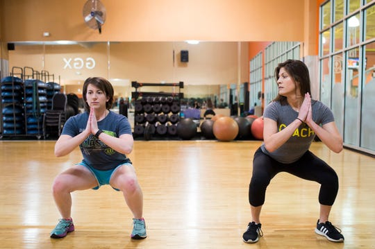 Fitness manager Deonna Walker and News Sentinel reporter Maggie Jones do air squats at Gold's Gym on Kingston Pike.