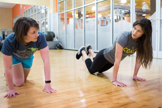 Alcoa Gold's Gym fitness manager Deonna Walker leads News Sentinel reporter Maggie Jones in a set of planks with shoulder taps at the Gold's Gym on Kingston Pike on Dec. 19, 2018.